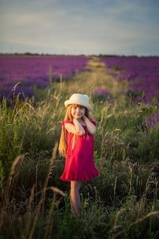 紫色の花を持つフィールドで深紅色のドレスの女の子、