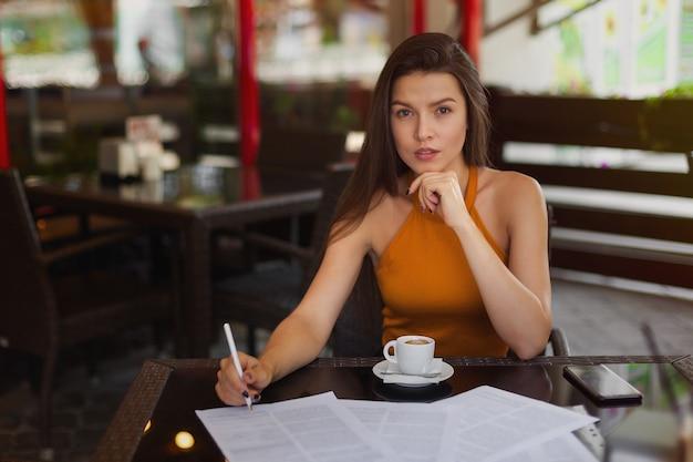 ビジネススタイル、ドキュメントと路上のカフェで一杯のコーヒーを飲みながらペンを持つ少女