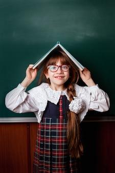 Школьница в школьной форме с книгой на голове