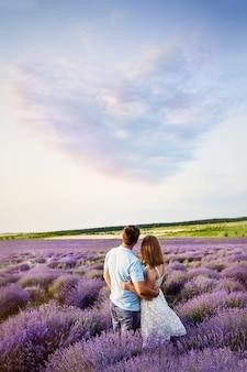 愛のカップルは絵のような風景を見てください。ラベンダー畑。日没。ハートの形の雲。