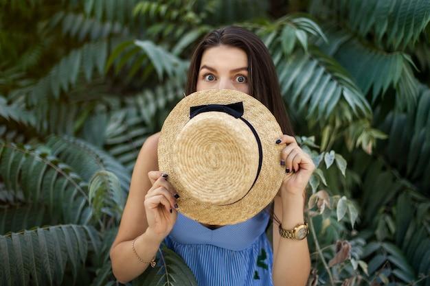 Путешественница. девушка прячется за шляпой, пялится в глаза, удивляется и восхищается. пальмовые деревья