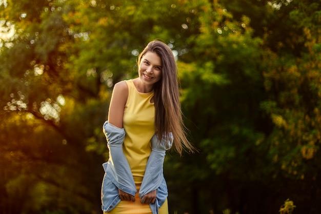 Счастливая девушка деревья. девушка смеется и радуется в желтом платье