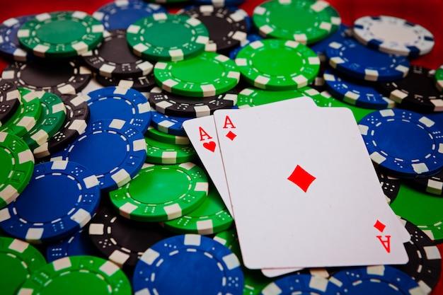 Два туза с червями и рубинами лежат на покерных фишках крупным планом