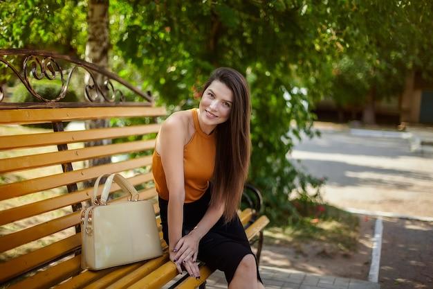 女子学生、笑みを浮かべて、公園のベンチで休んでバッグを持つ少女。