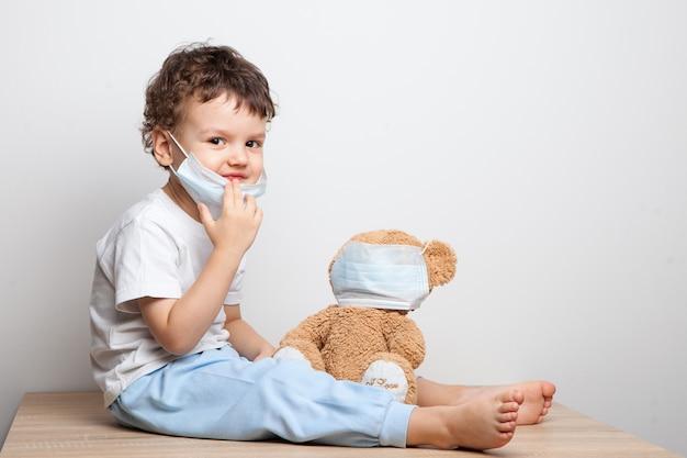 ウイルスやインフルエンザに対する予防策を子供に教える。赤ちゃん、医療マスクの少年は彼のテディベアグッズに医療マスクを置きます。愛する人の世話をします。基本的な衛生ルール