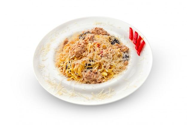 Острые спагетти из тунца с красным чили и сладким базиликом на белом блюде.