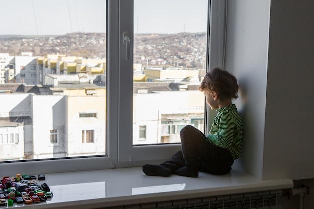 小さな男の子が窓枠に座って、窓の外を見る