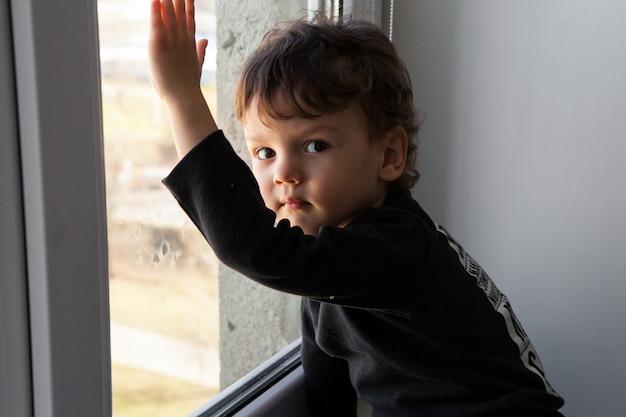 Потрет скучающего мальчика в комнате у окна.