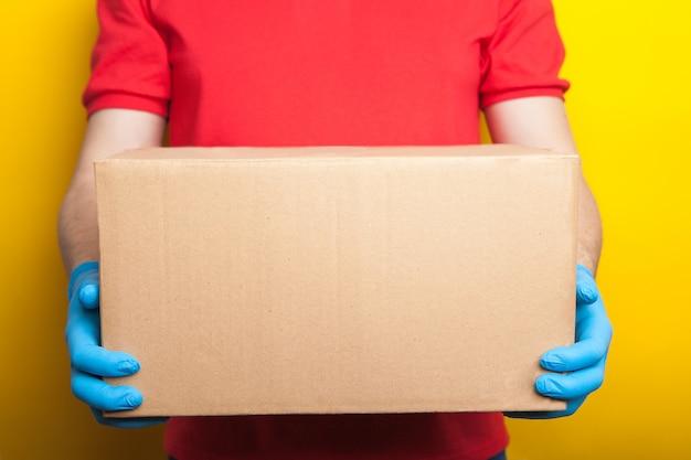 オンライン注文と配送。赤い制服とゴム製の医療用手袋の男は、明るい黄色の背景にボックスを保持しています。コロナウイルス検疫期間中の食品の配達。