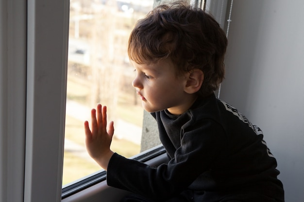 検疫。小さな男の子が窓枠に座って、退屈した窓の外を見ます。コロナウイルスのパンデミックによる検疫中の強制退去