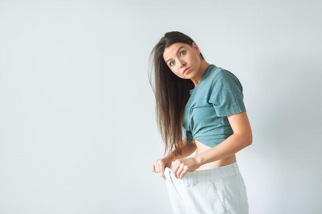 Потеря веса, здоровый образ жизни. молодая счастливая взволнованная женщина фитнес девушка с большими штанами, показывая, сколько веса она потеряла
