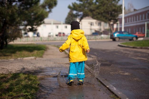 防水スプレースーツで水たまりに飛び乗って幸せな子供が街中を散歩します。