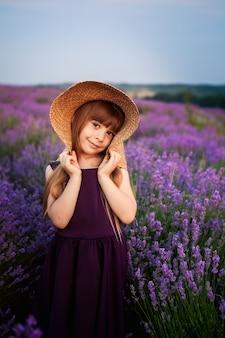Маленькая девочка пахнет кустами цветов гортензии в солнечном саду. цветущие цветы розовые, голубые, сиреневые. малыш в розовом платье, соломенная шляпа. романтическая концепция нежности, детства.