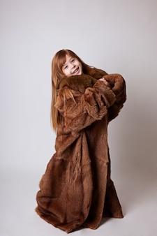 母の茶色のロングコートの少女