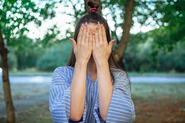 Прятки. девушка закрыла лицо руками. портрет крупным планом на закате. красивая молодая женщина на открытом воздухе прячет лицо, показывая ухоженные руки с маникюром.