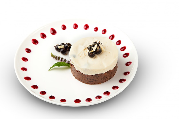 Кусок блинного торта с колпаком из ягод, облитый белым шоколадом на тарелке с бельгийскими кексами на белом столе