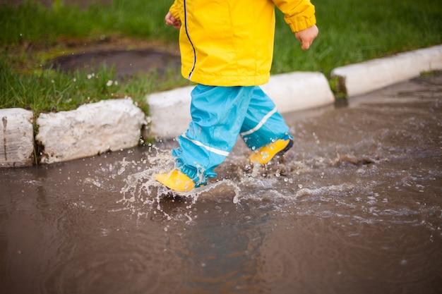 Весенние прогулки в любую погоду. ребенок бежит по лужам в резиновых сапогах и водонепроницаемом костюме, брызгая водой во все стороны. счастливое детство с веселыми прогулками.