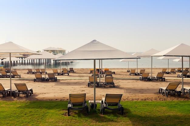 Линия шезлонги с зонтиками на пляже, перспектива. отель, летний отдых.