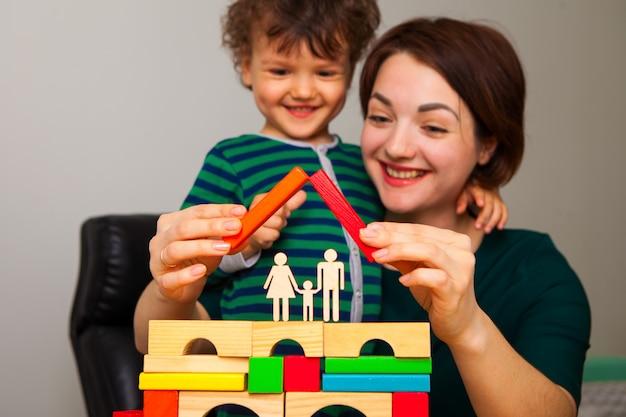 Счастливая мама и сын играют и строят дом для семьи. они положили крышу. женщина показывает мальчику и учит его, как важно проводить карантин дома.