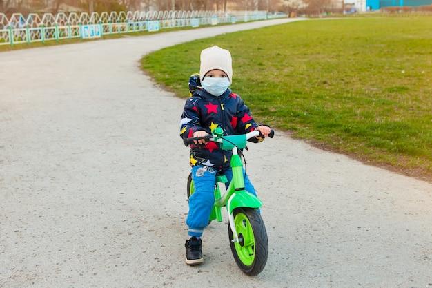 子供は路上で自転車に乗り、コロナウイルス感染を防ぐためのあらゆる予防策を講じています。