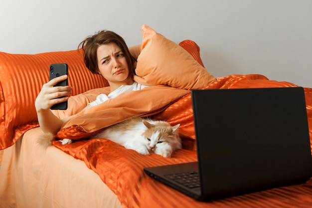Женщина смотрит на экран телефона недоволен, будильник лежал в постели. рядом на кровати лежит ноутбук и спит кот