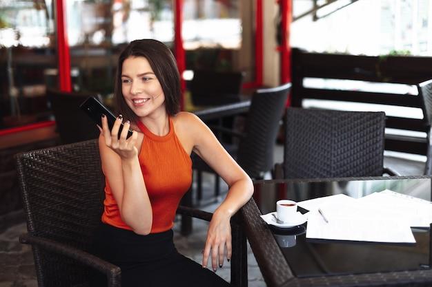 一杯のコーヒーのためのカフェで幸せな女の子。
