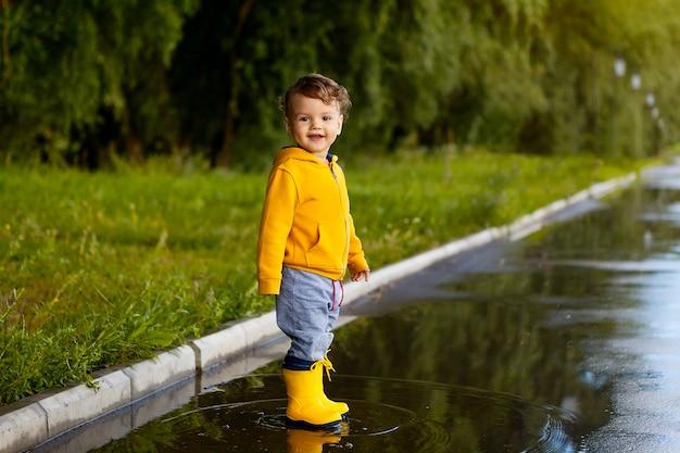 高められた免疫。雨の後、水たまりの上にゴム長靴で新鮮な空気の中で少年を歩きます。