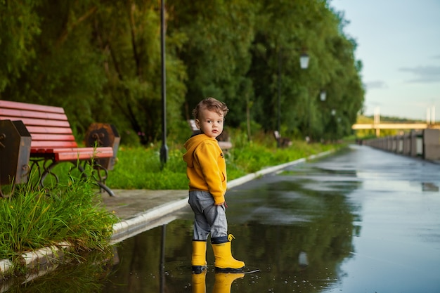 春の散歩に水たまりにゴム長靴で幸せな子供男の子。