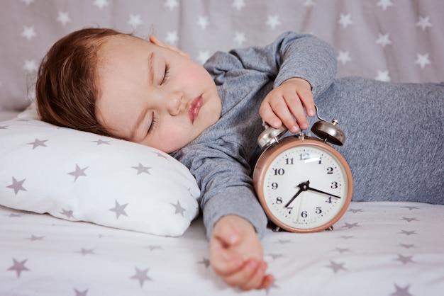 目覚まし時計とベビーベッドで眠っている赤ちゃん