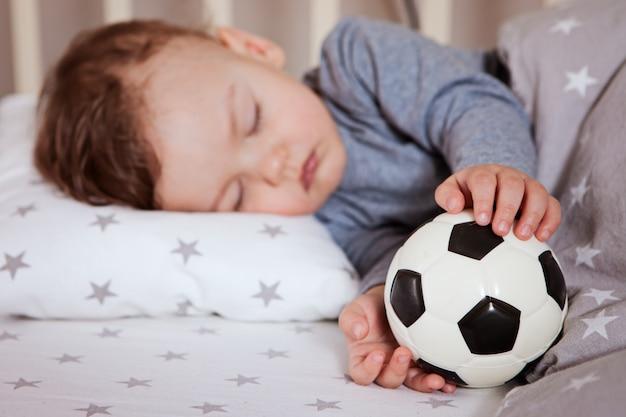 赤ちゃんは彼の手にサッカーをしたベビーベッドで眠っています。