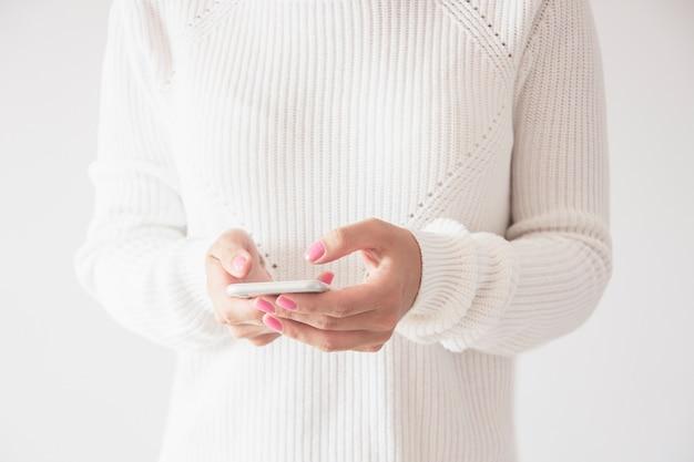 モバイルのスマートフォンを使用して、マッサージを送信する女性の正面のクローズアップ