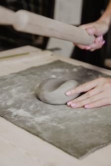 麺棒で粘土をモデリング若い女性