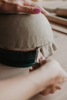 未完成のプレートから余分な粘土を切る若い女性