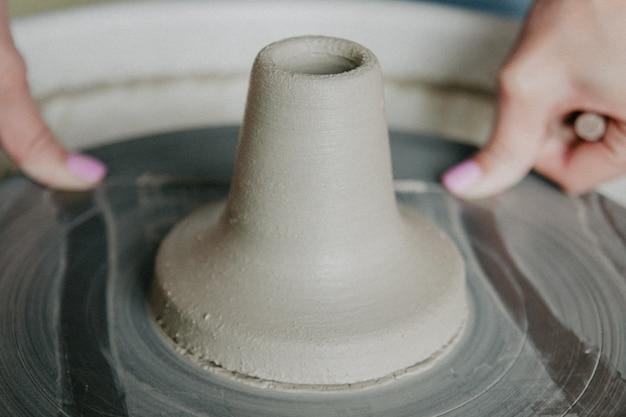 ワイヤーで粘土の花瓶を切る手