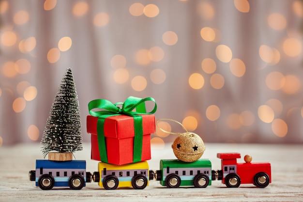冬のクリスマスの背景モミの木とミニチュアカラフルな電車。ホリデーグリーティングカード