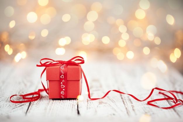 木製のテーブルに赤い弓リボンと紙のハートと赤いプレゼントボックス