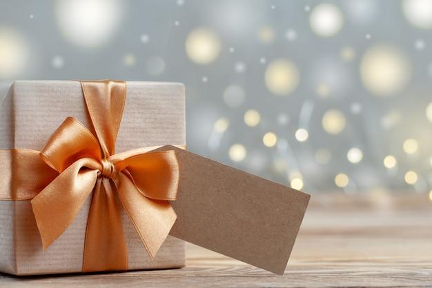 Подарочная коробка обернута крафт-бумагой и бантом. концепция праздника.