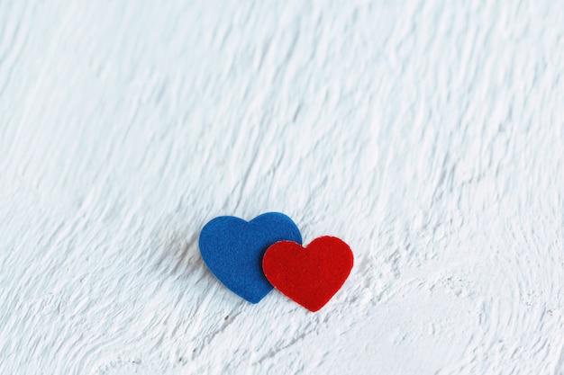 Красное сердце и синее сердце на белом фоне древесины. валентина да