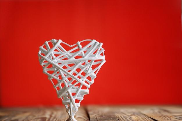 Белое сердце ручной работы из стержней на красном фоне. валентина да