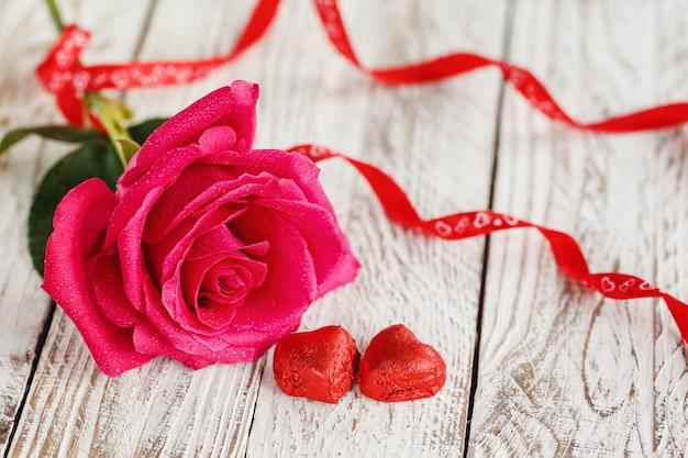 Красивая розовая роза на белом столе.