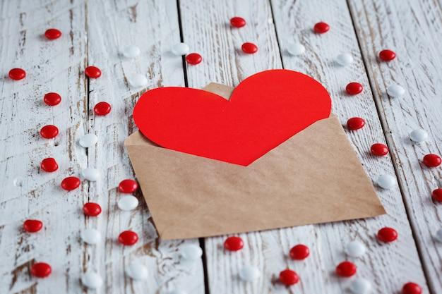 Простой конверт с красной бумажной сердечной валентинкой
