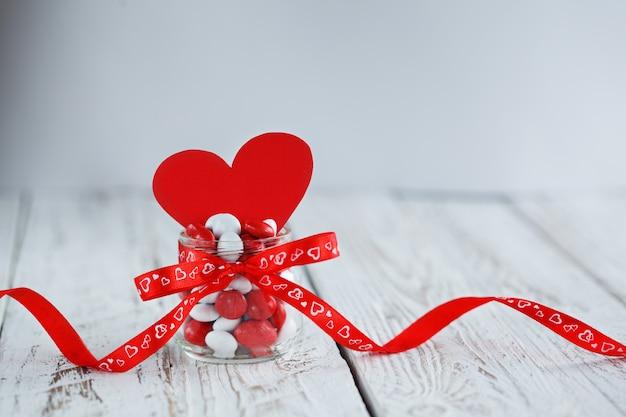 Красочный кувшин украшен красным бантом и красным бумажным сердцем. день святого валентина