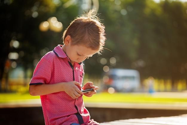 小さな子供は暖かい日当たりの良いダで遊ぶために彼の携帯電話に夢中