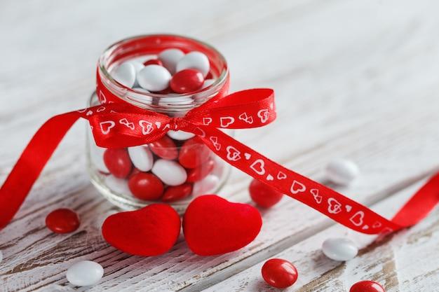 赤い弓の心で飾られたカラフルなキャンディーの瓶。バレンタインデーのコンセプト