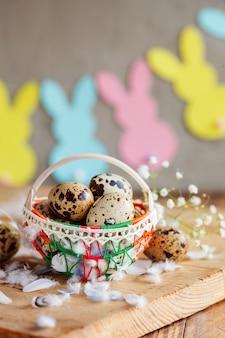 Пасхальная композиция из пасхальных перепелиных яиц в корзине и с гирляндой зайчика.