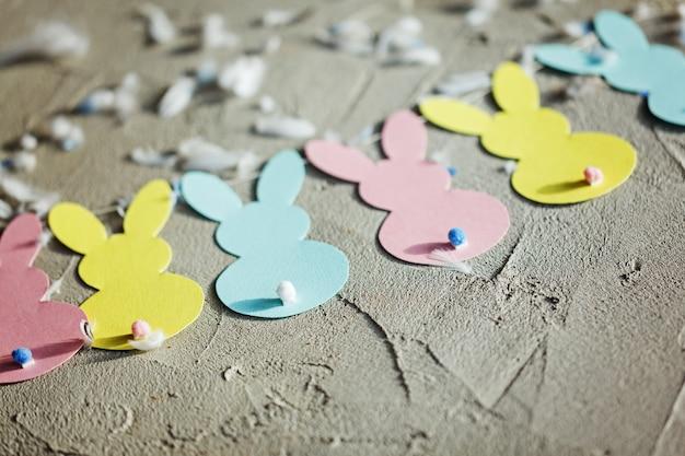 Гирлянда с цветной бумаги кроликов. концепция пасхальный заяц баннер. вид сверху
