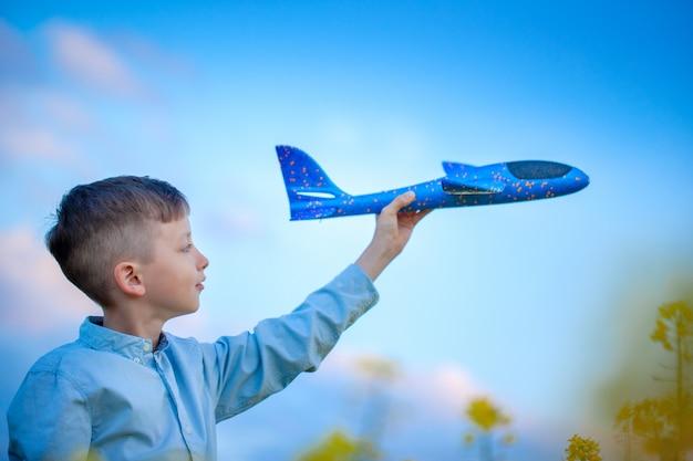 青い空と旅の夢の中でかわいい男の子がおもちゃの飛行機で遊ぶ。青いおもちゃの飛行機を持つ手。