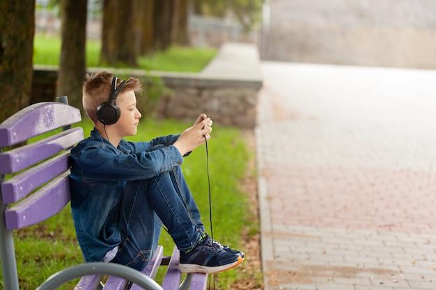 若い男が彼の携帯電話を屋外でチェックします。ヘッドフォンのティーンエイジャーは彼のスマートフォンを使用しています。