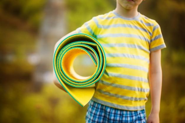 自然でスポーツをしているかわいい男の子。夏の公園で演習を行うスポーティな小さな男の子。