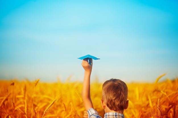 子供の紙の青い飛行機は黄色の麦畑と夏の日の青い空に手します。